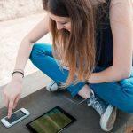 Visitor Stitching und Visitor Linking im Vergleich – junge Frau mit Smartphone und Tablet
