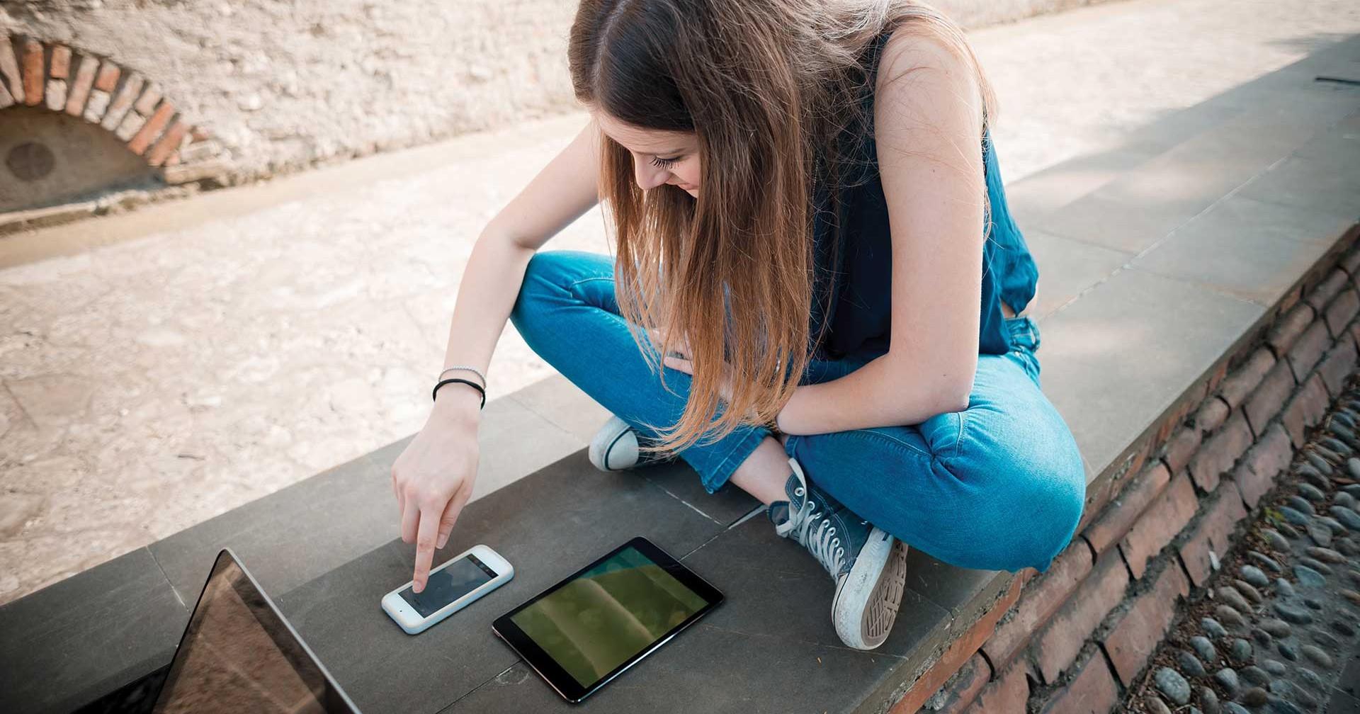 Chica usando un teléfono y una tableta