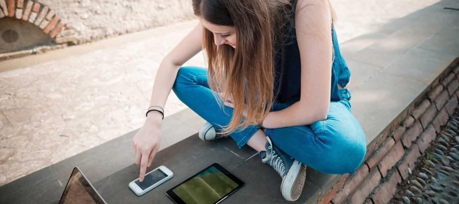 Jeune fille utilisant un téléphone et une tablette