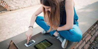Visitor Stitching vs Visitior Linking: jeune fille avec un téléphone mobile et une tablette